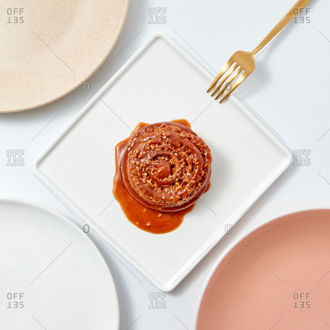 Freshly baked cinnamon bun with nuts and caramel in a square plate with a fork on a light background with space for text. Flat lay