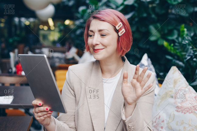 Attractive  fashionable woman with pink hair sitting in modern bar during a break at work, having a friendly family video call over tablet.