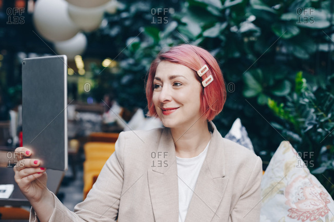 Candid moment, portrait of attractive  alternative woman sitting in modern bar full of plants during a break at work, having a friendly video call over tablet.