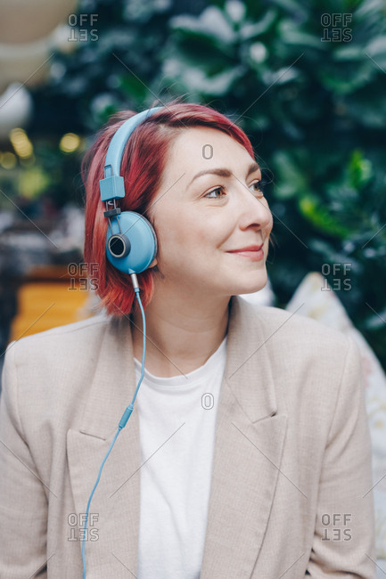 Authentic portrait of a beautiful woman with pink hair listening to music over headphones. Fashionable girl enjoying a break in a bar and listening to podcast show.