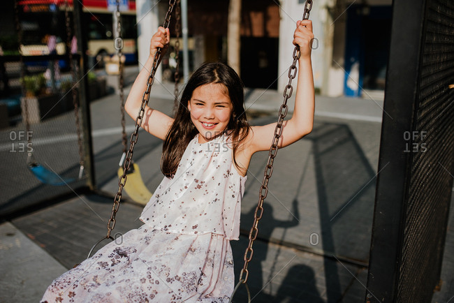 Adorable girl swinging on a swing set in a commercial district with bright afternoon light
