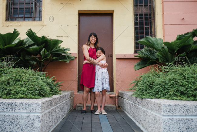 Mother and daughter posing in a hug outside a building in Kuala Lumpur