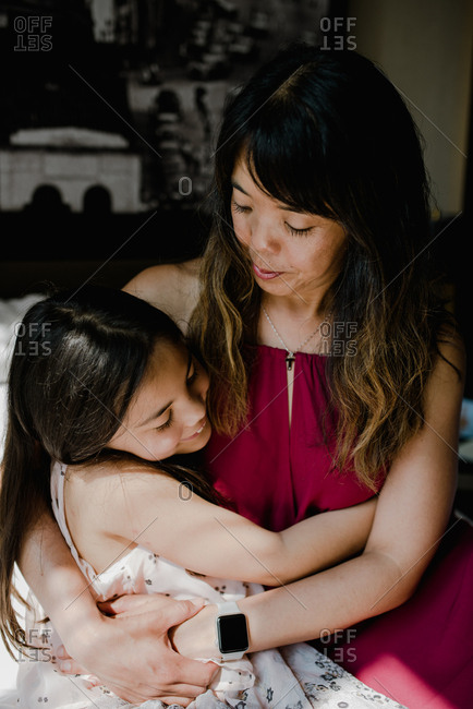 Asian mother and daughter hugging at home in dappled sunlight