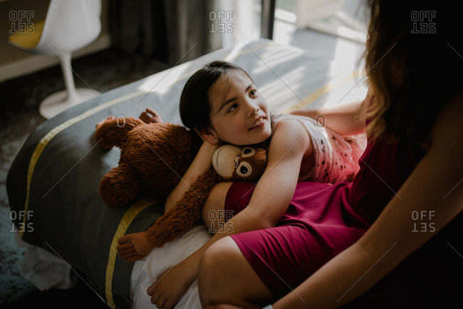 Young daughter looking up at mother while relaxing on a hotel bed with a stuffed animal monkey