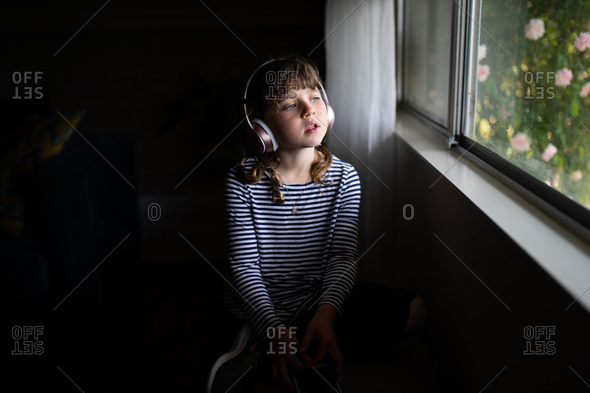 Girl with headphones looking out window