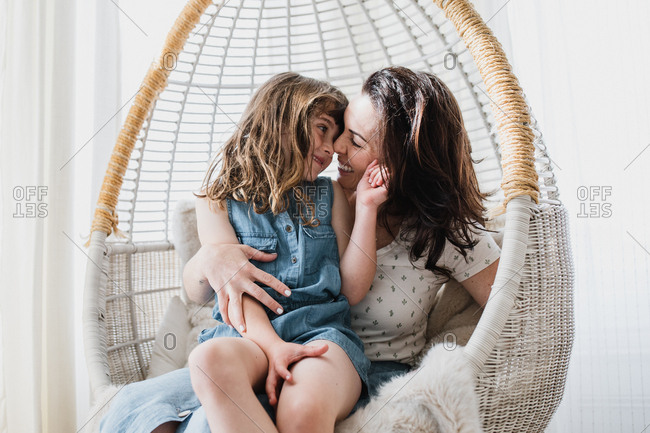 Mom and daughter in indoor swing chair