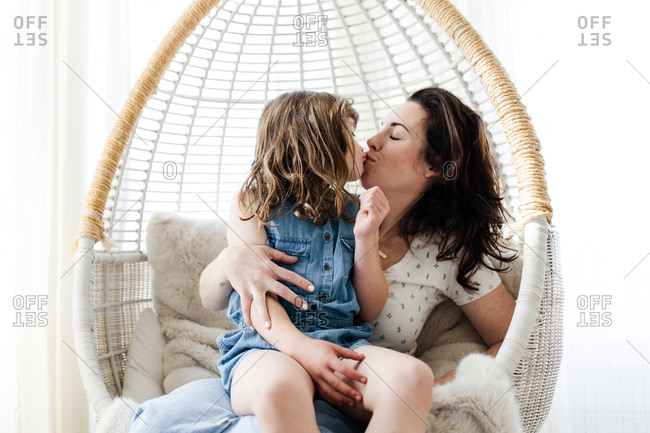 Mom and daughter in indoor swing chair kissing