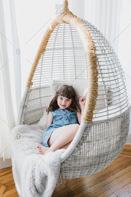 Girl resting in indoor swing chair