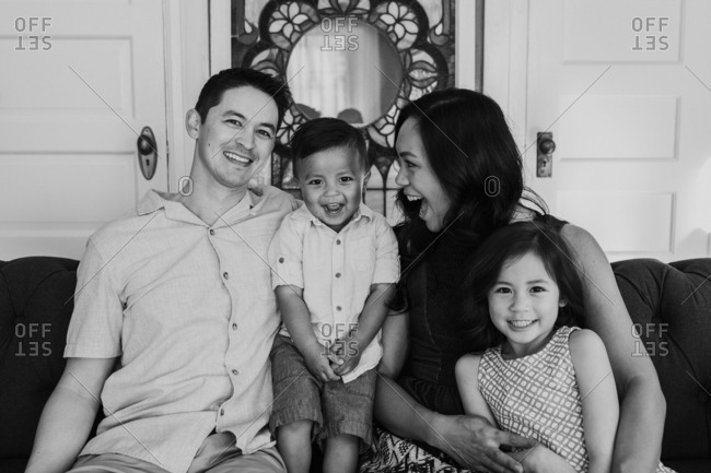 Family of four on couch in living room in black and white