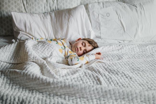 Boy sleeping in lemon pajamas on white bed