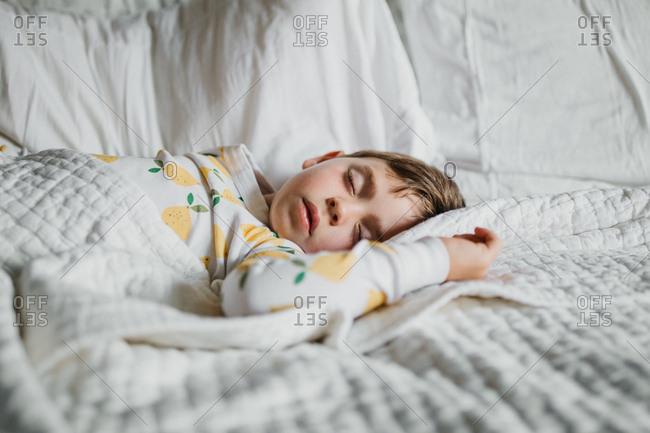 Boy asleep in lemon pajamas on white bed