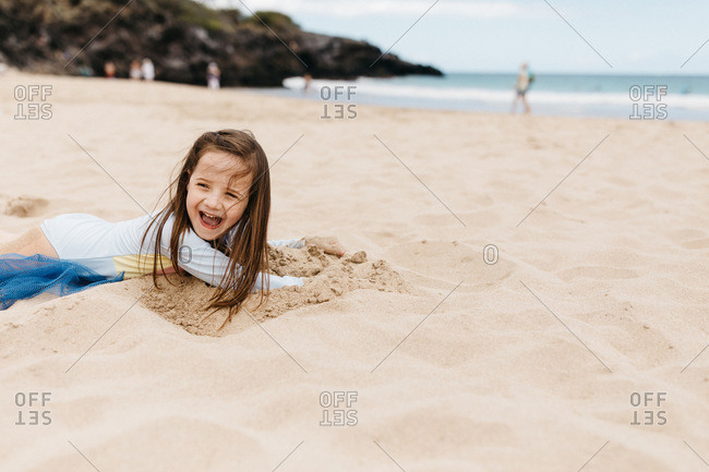 Little girl digging in the sand in Hawaii
