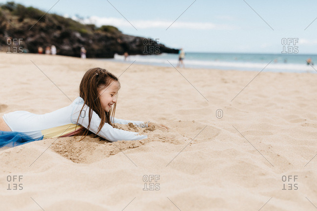 Girl digging in the sand on a beach in Hawaii