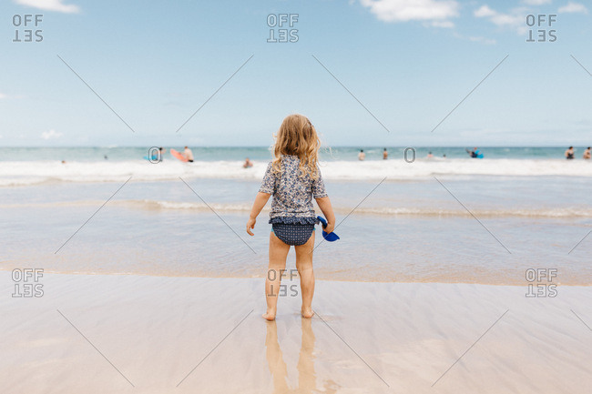 Rear view of a little girl standing in the water in Hawaii