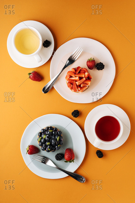 Overhead view of fruit tarts and tea
