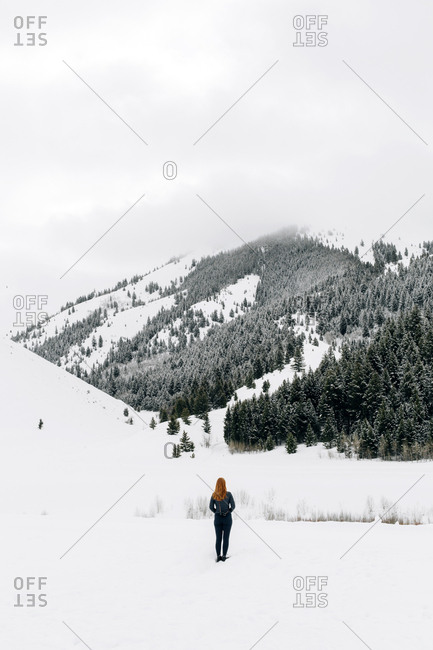 Redhead woman hiking in snow covered landscape, Idaho