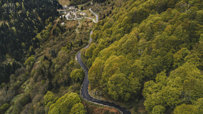 Aerial view of winding road in dense forest in the Pyrenees