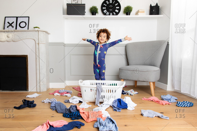 Playful boy in pajamas making mess with laundry basket