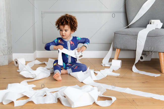 Boy plays with toilet paper rolls