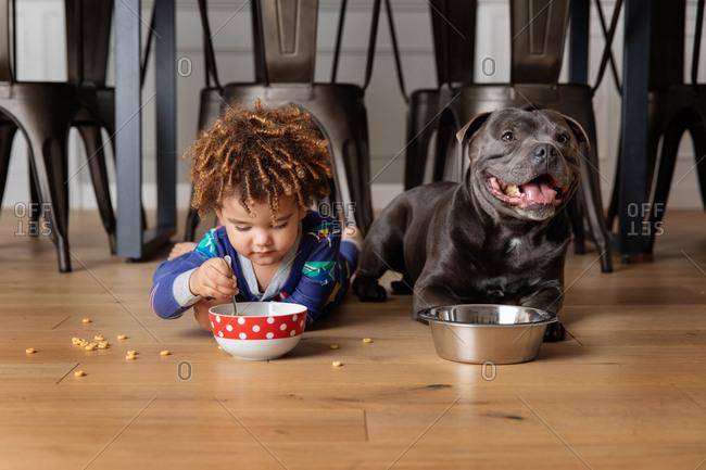 Boy eats with dog on floor