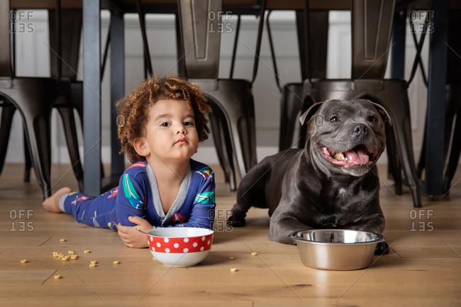 Boy and dog eat together on kitchen floor