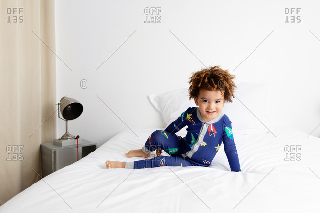 Smiling boy with afro hair poses on bed