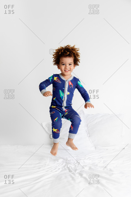 Smiling boy in pajamas jumping on bed