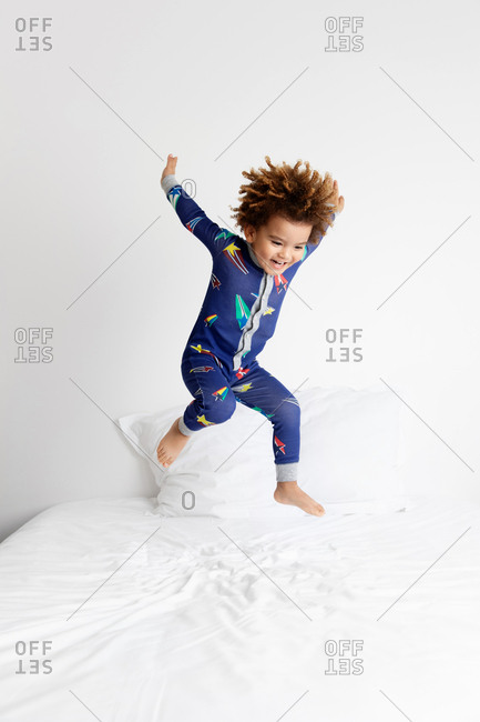 Smiling boy bouncing on bed