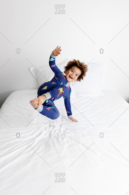 Happy boy jumping on bed