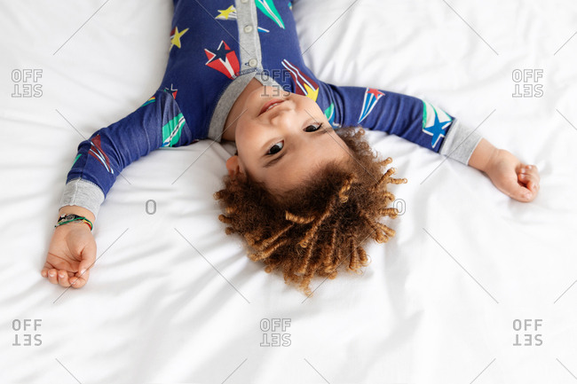 Smiling boy lying on bed upside down stretches arms