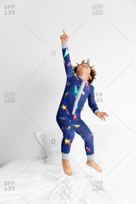 Young boy in pajamas jumps on bed