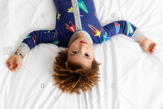 Boy with afro hair lies upside down on bed