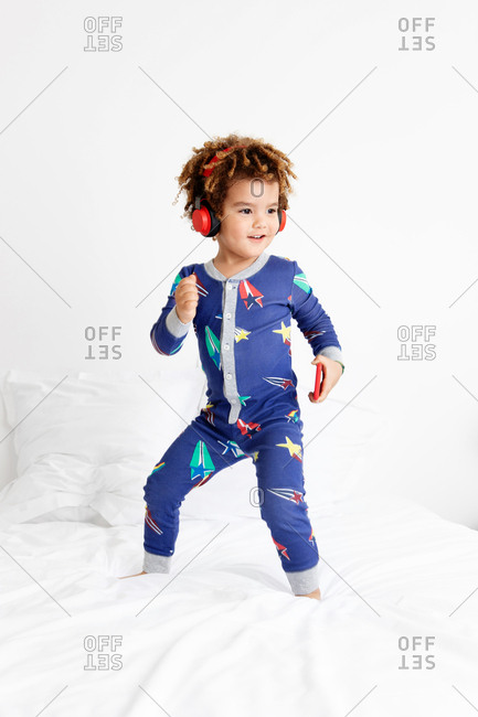Young boy dancing on bed with headphones holding mobile phone