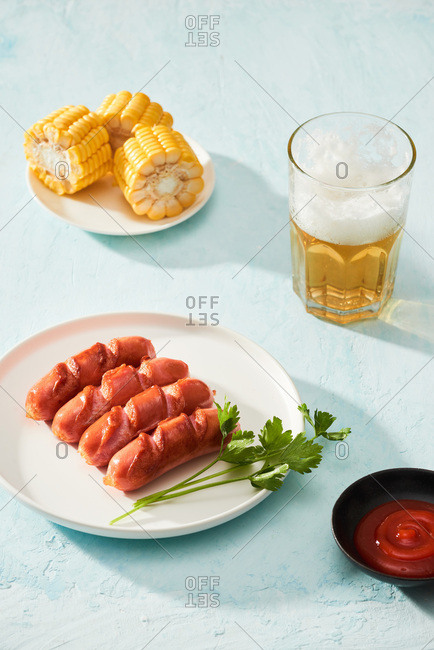 Grilled sausages with glass of beer and boiled corn on blue background