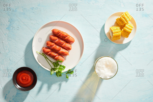 Overhead view of grilled sausages with glass of beer and boiled corn on blue background