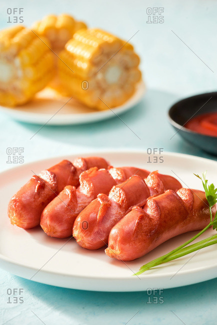 Close up of sausages and boiled corn on blue background
