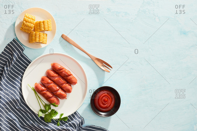 Boiled corn and grilled sausages on blue table. Top view with copy space