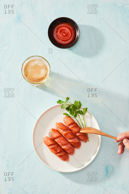 Grilled sausages with beer and ketchup on a white plate