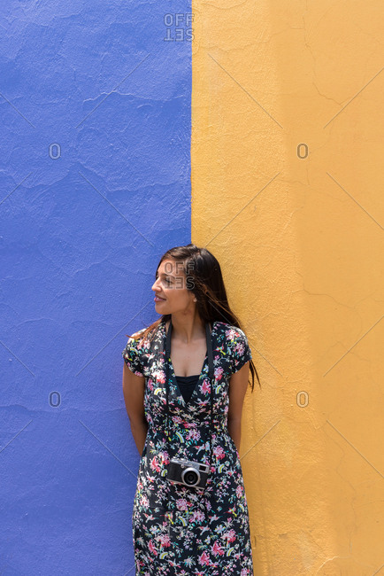 Woman with a summer dress in front of a bicolor wall in Cholula, Mexico