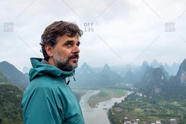 Man over the Li River and the karst landscape on a hilltop in Xingping, Guangxi Province, China