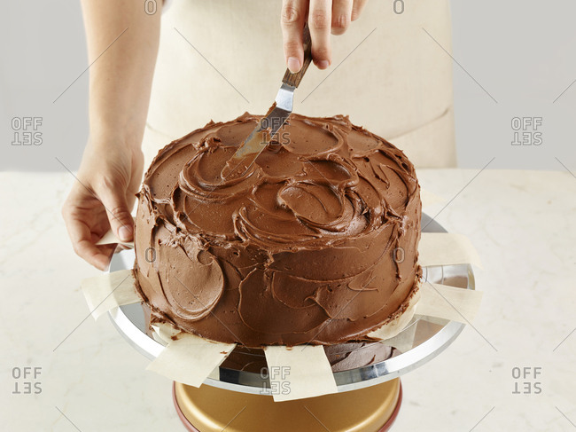 Baker frosting a chocolate cake