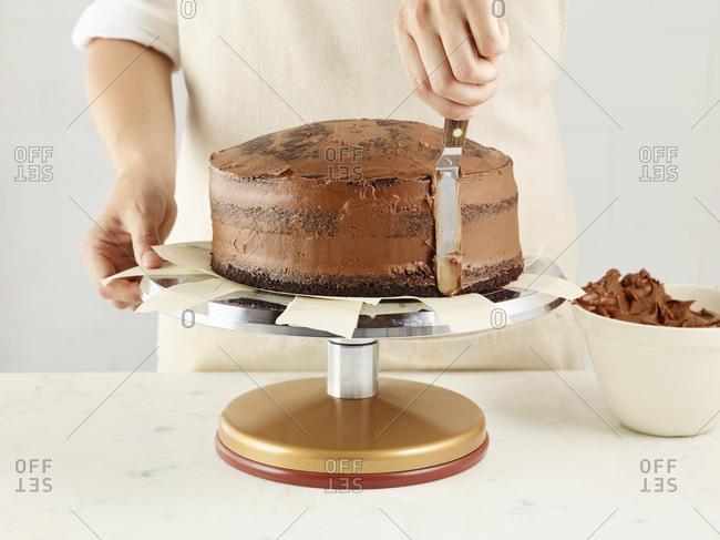 Baker icing a chocolate cake