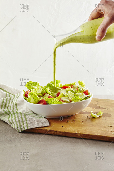 Hand pouring wasabi avocado dressing on salad
