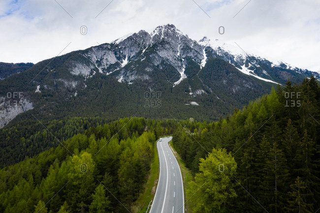 Road surrounded by lush green forest at the base of a mountain