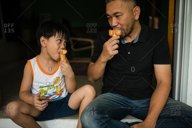 Father and son eating ice cream cones