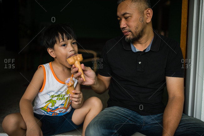 Father feeding son an ice cream cone