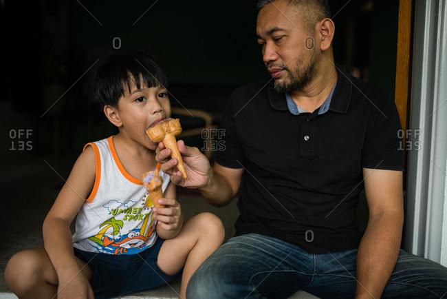 Father feeding son an ice cream cone