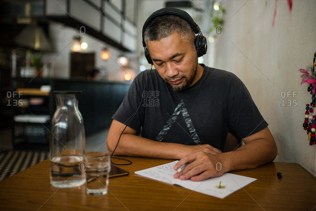 Man writing while listening to music on phone at cafe