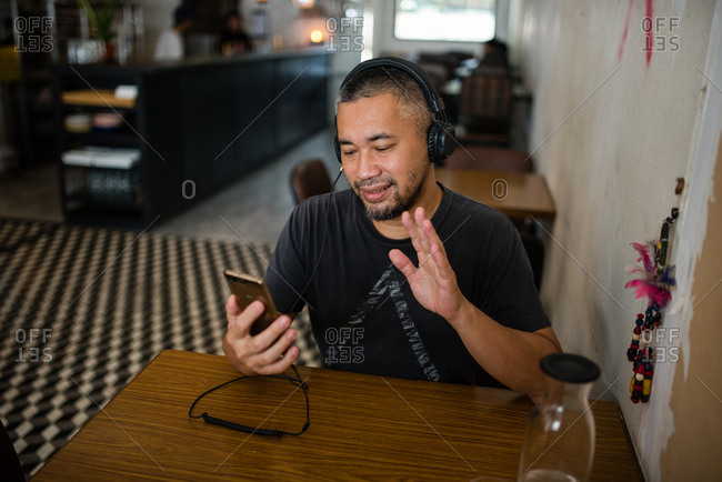 Man video chatting on phone at cafe while wearing headphones