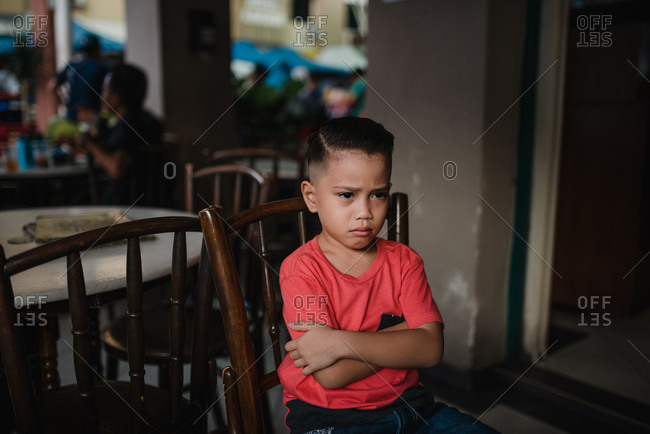 Young Asian boy sitting with arms crossed after haircut